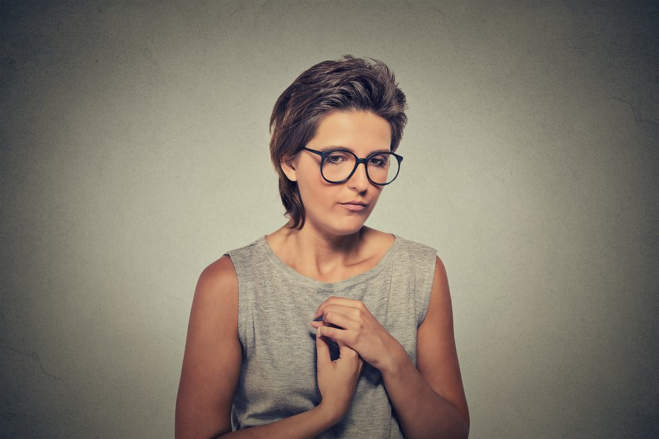 Lack of confidence. Shy young woman in glasses feels awkward
